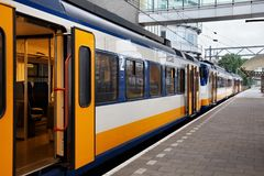 Yellow Dutch train on the Amsterdam Centraal station platform in morning. Centraal is the largest railway station of Amsterdam, Netherlands and a major national Stock Photos