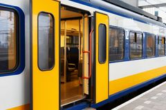 Yellow Dutch train on the Amsterdam Centraal station platform in morning. Centraal is the largest railway station of Amsterdam, Netherlands and a major national Stock Photo