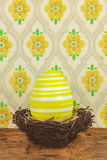 Yellow dyed big easter egg in a bird nest on a wooden table Royalty Free Stock Image