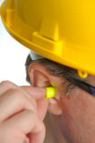Yellow earplug into the ear Royalty Free Stock Image