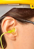 Yellow earplug into the ear Royalty Free Stock Photography
