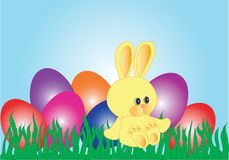 Yellow Easter Bunny. Sitting in the grass near colourful eggs Stock Photo