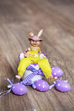 Yellow easter ceramic bunny with purple  eggs Royalty Free Stock Photography
