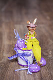 Yellow easter ceramic bunny with purple  eggs Stock Photo