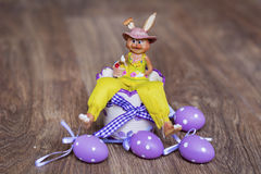 Yellow easter ceramic bunny with purple  eggs Royalty Free Stock Images