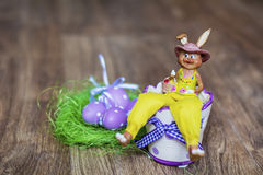 Yellow easter ceramic bunny with purple  eggs Royalty Free Stock Photos