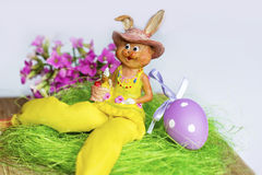 Yellow easter ceramic bunny with purple  eggs Royalty Free Stock Photo