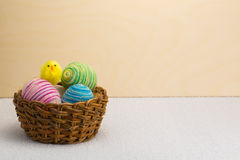 Yellow Easter chick and basket of Easter eggs Stock Photo