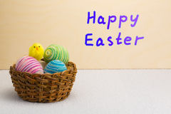 Yellow Easter chick and basket of Easter eggs Royalty Free Stock Images