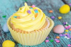 Yellow Easter cupcake with candy and sprinkles Royalty Free Stock Image