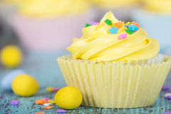 Yellow Easter cupcake with candy and sprinkles Royalty Free Stock Photos