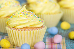 Yellow Easter cupcake with sprinkles and candy eggs Stock Image