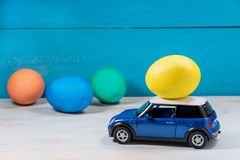 Easter egg in toy car on a blue background. Yellow Easter egg in blue toy car with white roof on a blue background stock photography