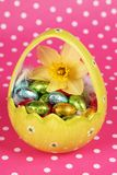 Yellow easter egg with chocolate. On dotted background Royalty Free Stock Photos