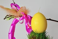Yellow easter egg on grassy round surface, decorative whip korbash in background. Royalty Free Stock Image