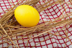 Yellow easter egg in the hay on a kitchen towel Stock Photo