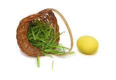 Yellow easter egg with a basket and grass. Yellow easter egg with an overturn basket full grass Royalty Free Stock Photo