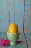 Yellow Easter Egg in a Pastel Green Egg Holder. Yellow Easter Egg in a Pastel Green Egg Cup with pink and purple Easter grass on a wooden board royalty free stock photo