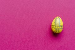 Yellow Easter egg on pink paper background.  royalty free stock photography