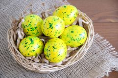 Yellow Easter eggs in basket. On linen fabric brown. Wooden brown background stock photos