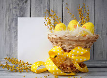 Yellow easter eggs in a basket. On a wooden background Stock Images