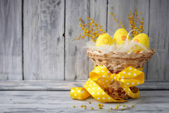 Yellow easter eggs in a basket. On a wooden background Stock Photos