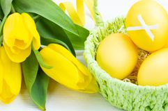 Colorful Easter eggs in green basket and bouquet of tulips on white wooden background. Easter holiday concept stock photos
