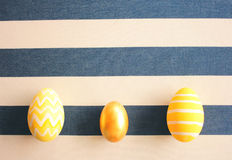 Yellow easter eggs on striped background with retro filter effec Stock Image