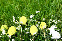 Yellow easter eggs, white rabbit and flowers are on fresh spring grass in the garden. Stock Images