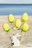 Yellow easter eggs, wooden rabbit are on the beach with sea. Royalty Free Stock Photo