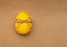 Yellow egg with bowknot on kraft background Royalty Free Stock Photos