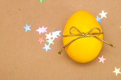 Yellow egg with bowknot on kraft background Stock Image