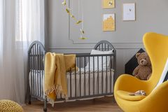 Yellow chair and, brown teddy bear and grey wooden crib with blanket in classy baby bedroom. Yellow egg chair and, brown teddy bear and grey wooden crib with royalty free stock photo