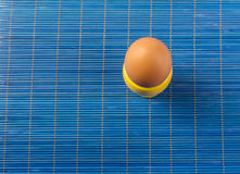 Yellow egg cup  on blue Royalty Free Stock Photo