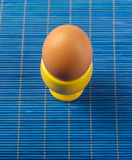 Yellow egg cup  on blue Stock Image