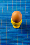 Yellow egg cup  on blue Royalty Free Stock Images