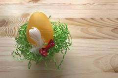 Yellow egg decorated with red bow and white feather Stock Photos
