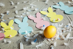 Yellow egg and Garland with colorful paper rabbits and feathers on concrete background. Concept Easter. Top view. Stock Photography