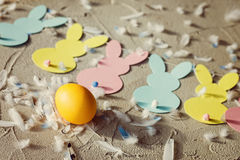 Yellow egg and Garland with colorful paper rabbits and feathers on concrete background. Concept Easter. Top view. Stock Image