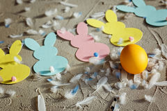 Yellow egg and Garland with colorful paper rabbits and feathers on concrete background. Concept Easter. Top view. Stock Photos