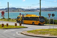 A yellow electric bus waits at the terminus by the side of Lyall Bay, Wellington, New Zealand royalty free stock photos