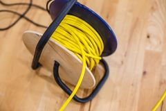 Yellow electric wire extension cord on the reel. Black Royalty Free Stock Photo