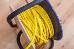 Yellow electric wire extension cord on the reel. Black Royalty Free Stock Images