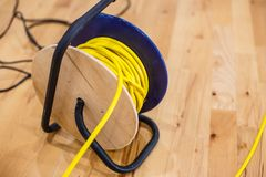 Yellow electric wire extension cord on the reel. Black Stock Photos