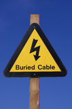 Yellow electrical hazard sign. Yellow buried electrical cables warning sign against blue sky royalty free stock images