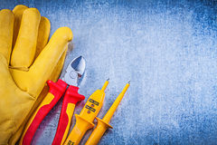 Yellow electrical tester safety gloves red nippers on metallic b Royalty Free Stock Photo