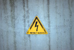 Yellow electricity warning sign on a weathered background Royalty Free Stock Photos