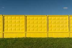 Yellow embossed concrete fence, green grass and blue sky. Abstract background Royalty Free Stock Images
