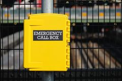 Yellow emergency call box. At a fence of construction site stock image