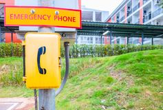 A yellow emergency phone box outdoor in the park.  stock photos
